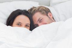掩藏在鸭绒垫子下的夫妇 免版税库存图片