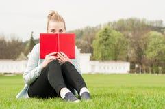 掩藏她的与书的年轻快乐的女性面孔 库存图片