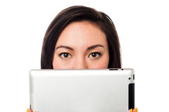 掩藏她的与片剂设备的亚洲模型面孔 免版税库存照片