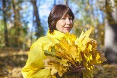 掩藏她的在一抱黄色澳大利亚后的年长可爱的妇女面孔 免版税图库摄影