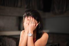 掩藏她的在她的手后的妇女的画象面孔 免版税库存照片