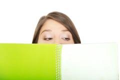 掩藏她的在笔记本后的妇女面孔 免版税库存图片