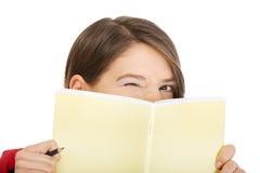 掩藏她的在笔记本后的妇女面孔 免版税库存照片