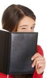 掩藏她的在笔记本后的妇女面孔 库存图片