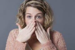 掩藏她的微笑的快乐的20s女孩困窘由情感 免版税库存照片