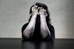 掩藏她的面孔的Sorrowfull妇女在手 免版税库存图片