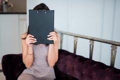 掩藏她的面孔behide的美丽的年轻女人地图 图库摄影