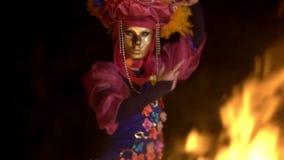掩藏面孔的一套特别衣服和一个金黄面具的黑暗的明亮夜灼烧的火跳舞的奥秘女孩 股票视频