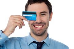 掩藏他的与信用卡的商人眼睛 免版税库存照片