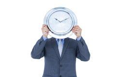 掩藏他的与白色时钟的商人面孔 免版税库存图片