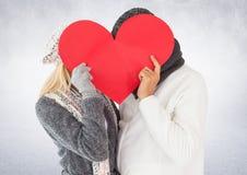 掩藏他们的在红色心脏后的夫妇面孔 免版税图库摄影