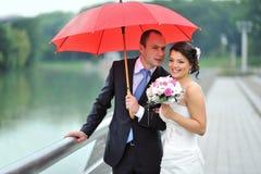掩藏从雨的愉快的婚礼夫妇 免版税图库摄影