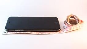 措施磁带和手机 免版税库存图片