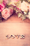 措辞与玫瑰色花的爱在木桌上, 免版税库存图片