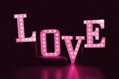 措辞从大信件的爱与在黑暗的背景的发光的电灯泡 库存图片