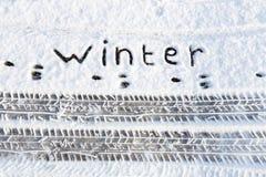 措辞冬天和轮胎轨道在雪在路 库存照片
