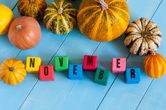 措辞在儿童的玩具立方体和南瓜的11月  库存图片