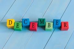 措辞在儿童的玩具立方体的12月在木农村 免版税图库摄影