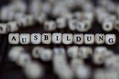 措辞在木立方体或块-教育背景的AUSBILDUNG 木头ABC 免版税库存照片