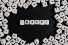 措辞在木立方体的损失在一张黑木桌上 免版税库存图片