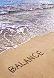 措辞在海滩沙子写的平衡,与海波浪在背景 免版税库存照片