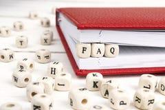 措辞在笔记本的木块写的常见问题解答在白色木ta 免版税库存照片