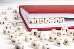 措辞在红色笔记本的木块写的争执在白色w 免版税库存照片