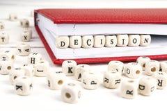措辞在红色笔记本的木块写的决定在白色 免版税库存图片