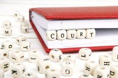 措辞在红色笔记本的木块写的法院在白色求爱 免版税库存照片