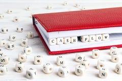 措辞在红色笔记本的木块写的现金流动在whi 免版税库存图片