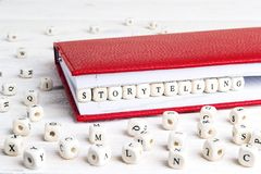 措辞在红色笔记本的木块写的讲故事在w 图库摄影