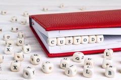 措辞在红色笔记本的木块写的Custidy在白色w 图库摄影