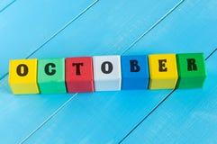 措辞在颜色木立方体的10月与浅兰 免版税库存照片