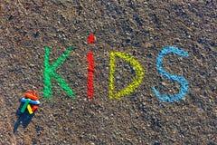 措辞孩子写与五颜六色的蜡笔在沥青,地面 免版税库存图片