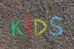 措辞孩子写与五颜六色的蜡笔在沥青,地面 库存照片