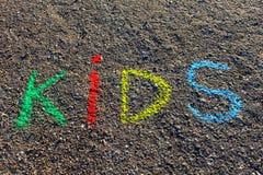措辞孩子写与五颜六色的蜡笔在沥青,地面 免版税库存照片