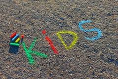 措辞孩子写与五颜六色的蜡笔在沥青,地面 免版税图库摄影