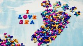 措辞我爱海`组成由在蓝色和白色背景和一只脚的多彩多姿的木信件组成由多彩多姿的s的` 免版税库存图片