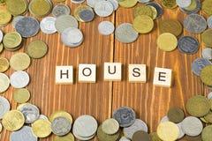 措辞木立方体的房子与硬币框架在木背景 安置的财政概念的储款计划 免版税库存图片