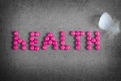 措辞桃红色药片和胆怯做的健康在灰色背景 免版税图库摄影