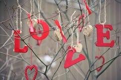 措辞爱和心形的装饰品在树 图库摄影