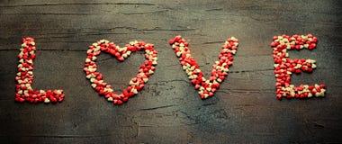 措辞用小糖果心脏做的爱,桃红色,红色,白色颜色,在黑暗的背景 华伦泰` s日概念 顶视图 库存图片