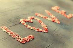 措辞用小糖果心脏做的爱,桃红色,红色,白色颜色,在黑暗的背景 华伦泰` s日概念 顶视图 免版税库存图片