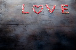 措辞用小糖果心脏做的爱,桃红色,红色, whie颜色,在黑暗的背景 华伦泰` s日概念 顶视图 库存图片