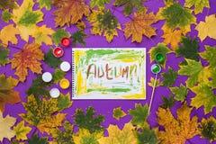 措辞秋天,得出被在一个册页的油漆在紫罗兰色背景 库存图片