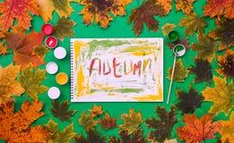 措辞秋天,得出被在一个册页的油漆在绿色背景 库存图片