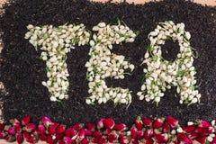 措辞茶由在黑茶叶的干茉莉花花蕾制成与疏散的干红色玫瑰花 免版税库存图片