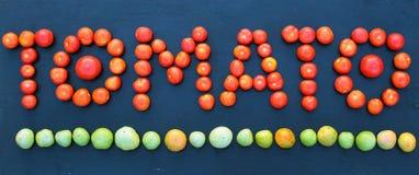 措辞蕃茄写用绿色和红色蕃茄在木板 免版税库存图片