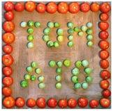措辞蕃茄写用绿色和红色蕃茄在木backgr 图库摄影