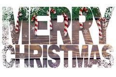 措辞`圣诞快乐`,与装饰棒棒糖的卡片在与绿色冷杉分支的木背景 免版税图库摄影
